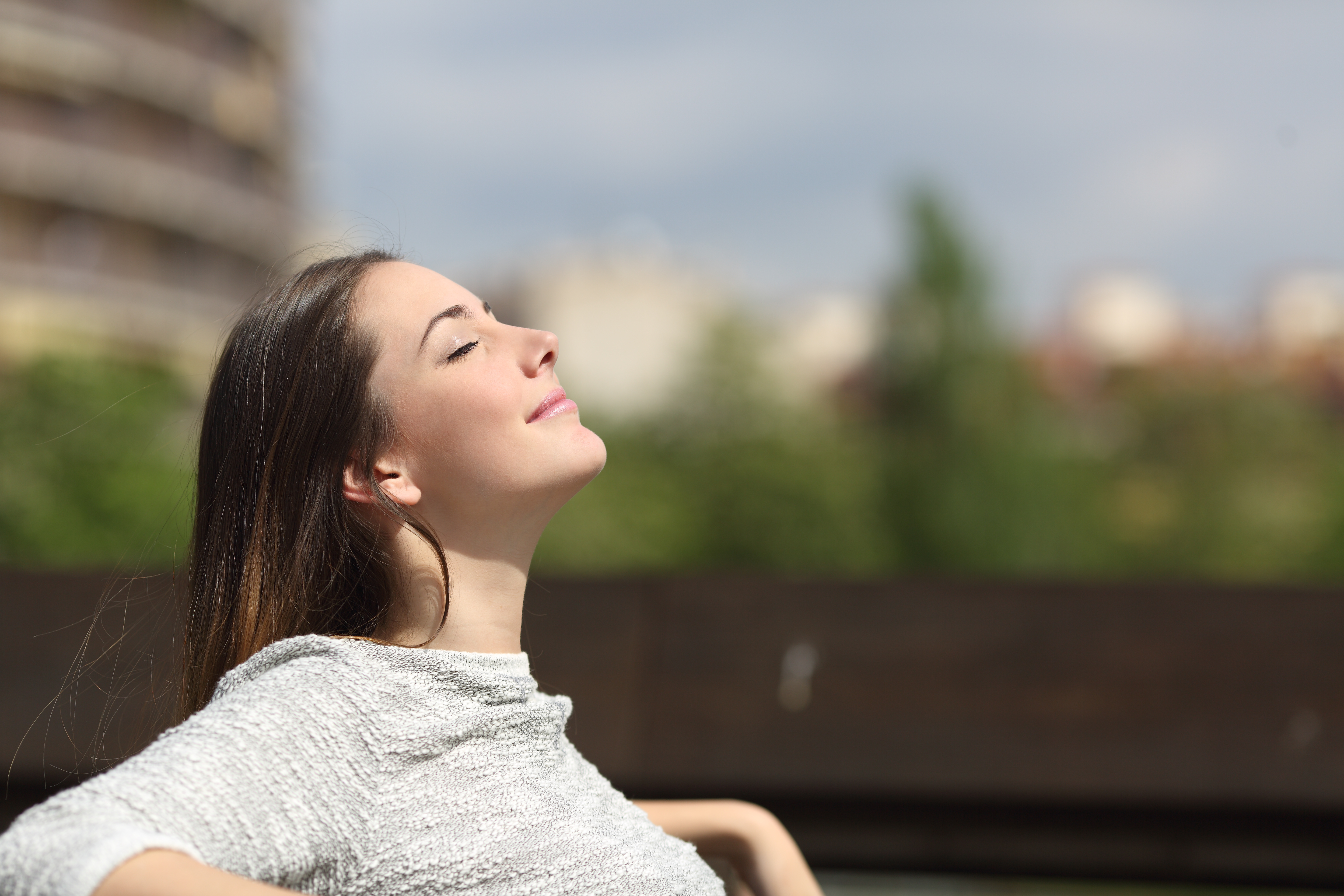 Image of a woman breathing calmly while basking in the sun.