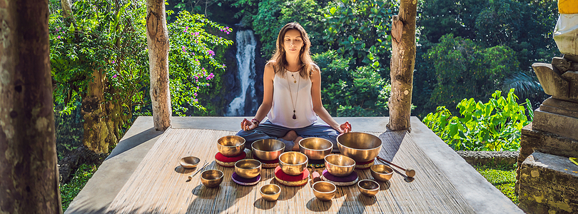 Woman playing on Tibetan singing bowl while sitting on yoga mat against a waterfall.